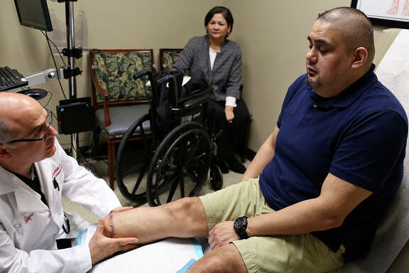 Dr. Boulos Toursarkissian inspects the leg of Isaac Rodriguez while Rodriguez's mother, Anita Rodriguez, watches at Peripheral Vascular Associates in San Antonio on Feb. 28, 2018.