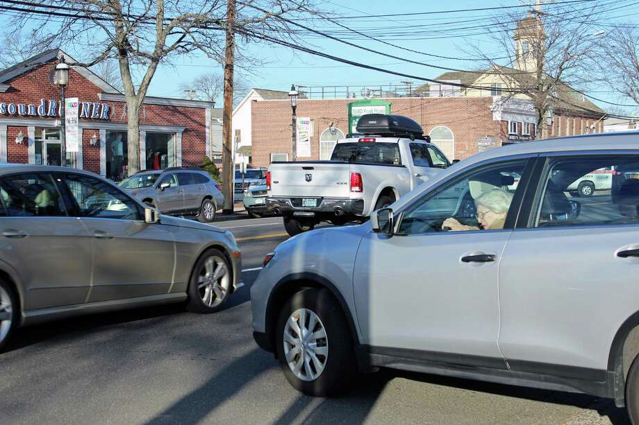 A driver waits to make a right turn out of a parking lot onto the Post Road. Photo: Genevieve Reilly / Hearst Connecticut Media / Fairfield Citizen
