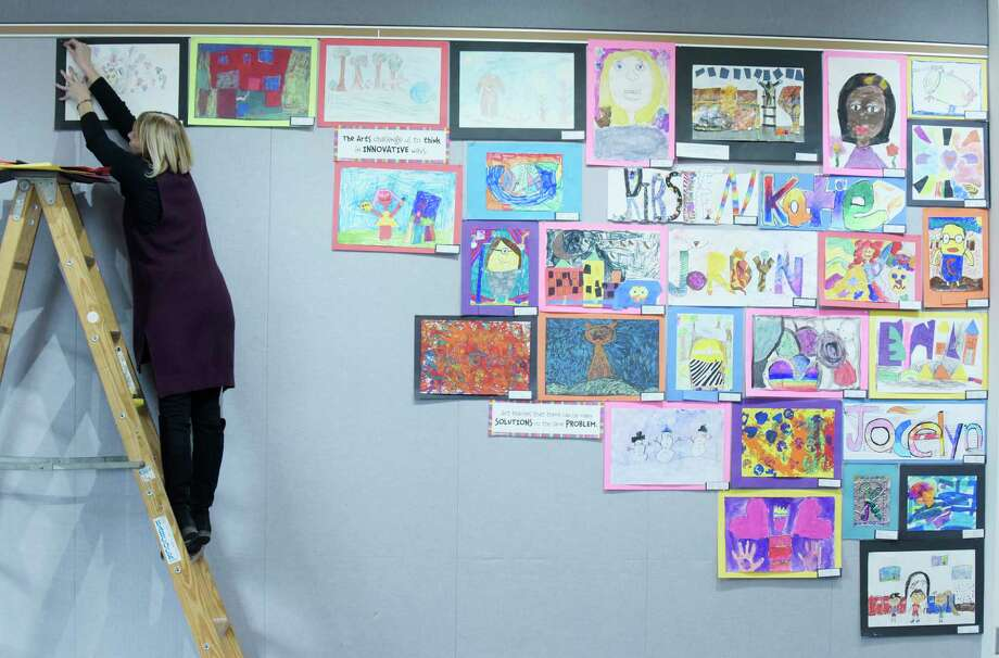 Guilderland Central School District art teacher, Susan Bollentin, works on hanging her elementary school student's artwork at the Guilderland Public Library on Tuesday, March 20, 2018, in Guilderland, N.Y. Bollentin teaches at Guilderland Elementary School.  (Paul Buckowski/Times Union) Photo: PAUL BUCKOWSKI / (Paul Buckowski/Times Union)