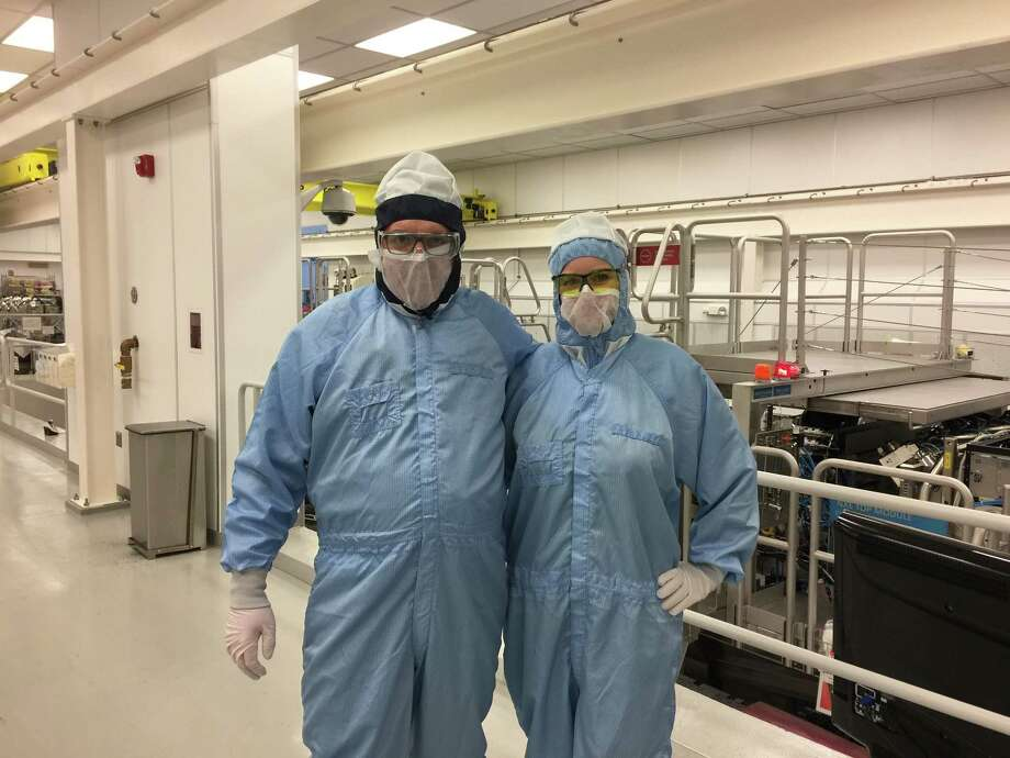Times Union reporter Larry Rulison, left, at ASML's manufacturing clean room in Wilton, Conn. on Monday, March 19, 2018. At right is ASML publicist Amy Rice. ASML is expanding its facilities as it ramps up making extreme ultraviolet lithography machines used to make cutting edge computer chips. Photo: ASML