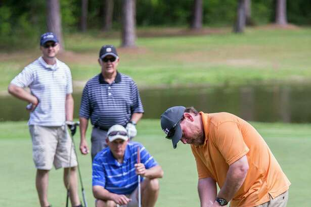 Darrell Thompson putts as his team looks on during the Crosby Huffman Chamber of Commerce's Tees-N-Tails golf tournament April 4, 2014, at Red Wolf Run Golf Club in Huffman. (Photo by ANDREW BUCKLEY/The Observer)