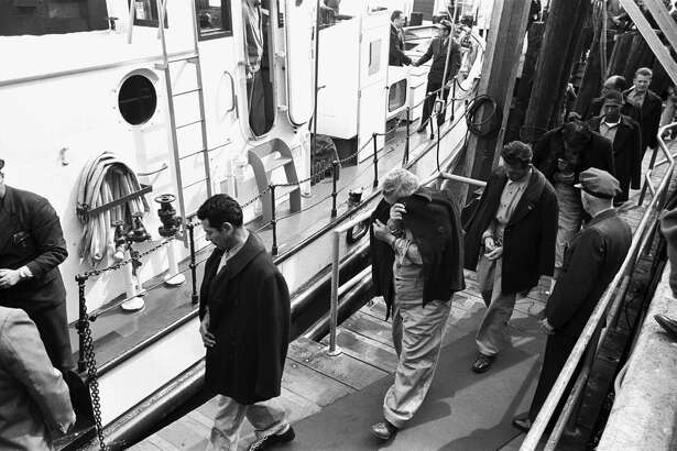Inmates of Alcatraz are escorted by guards onto a boat to be transferred to another federal prison after the closure of Alcatraz in 1963.