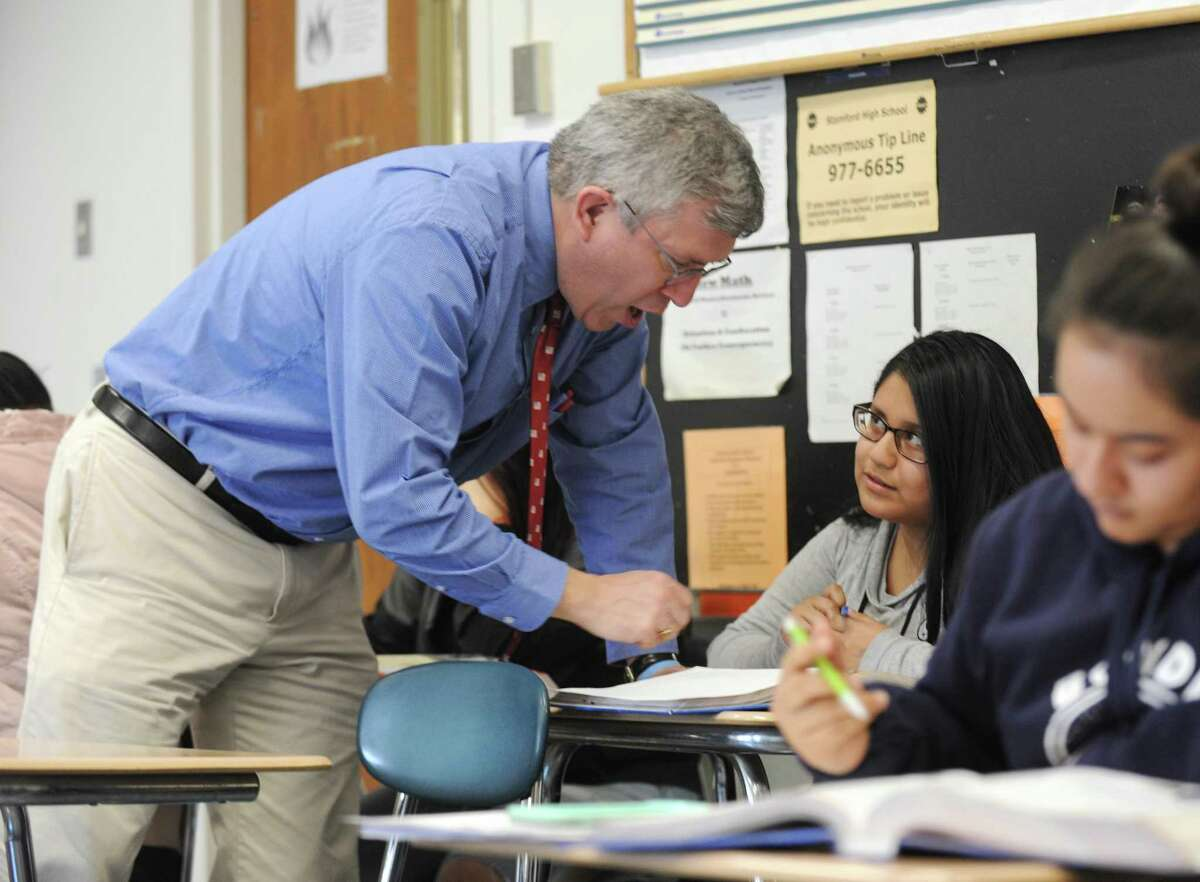 Doug MacLehose helps junior Nicole Gonzalez-Franco in U.S. history class at Stamford High School in Stamford, Conn. Thursday, March 15, 2018. MacLehose often focuses on immigration in his history classes taught at Stamford High, which has a large percentage of first- and second-generation immigrants.
