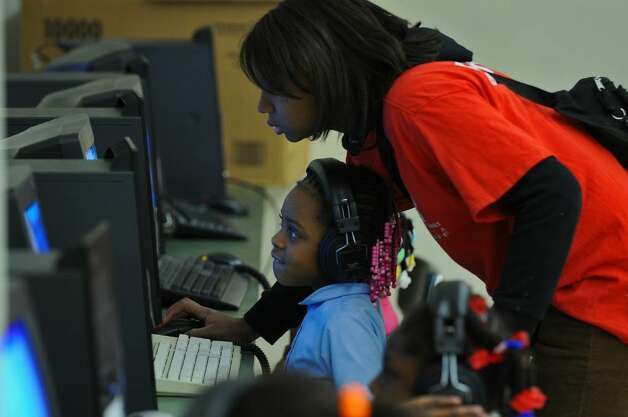 Child care counselor Taiwana Clark helps Zyiona Townsend, 6, in the computer lab at the Sheridan Preparatory Academy in Albany on Dec.  17, during the YMCA afterschool program there. (Philip Kamrass / Times Union) Photo: PHILIP KAMRASS