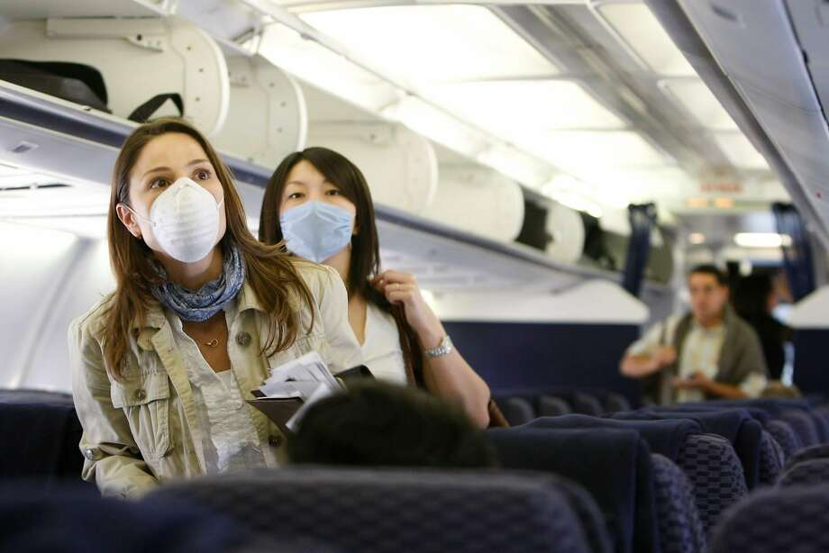 Airports and airlines are encouraging and in many cases mandating the use of masks for both passengers and staff. Photo: Julio Cortez, Chronicle