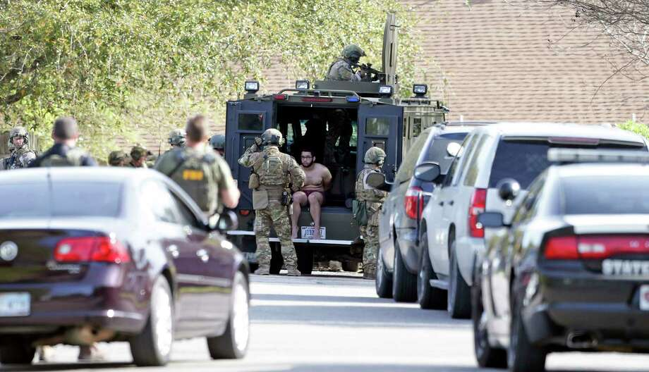 An individual is detained as FBI SWAT teams move into a residence at the scene of Walnut and 2nd Street in Pflugerville where bombing suspect lived  on March 21, 2018. Austin police announced Wednesday afternoon that two roommates of the Austin bombing suspect were detained and questioned. As of 1:30 p.m. police were not planning to release the two names as they were not arrested. Photo: Tom Reel, San Antonio Express-News / 2017 SAN ANTONIO EXPRESS-NEWS