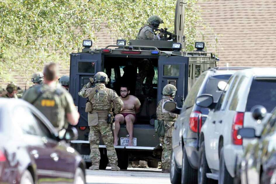 An individual is detained as FBI SWAT teams move into a residence at the scene of Walnut and 2nd Street in Pflugerville where bombing suspect lived  on March 21, 2018.