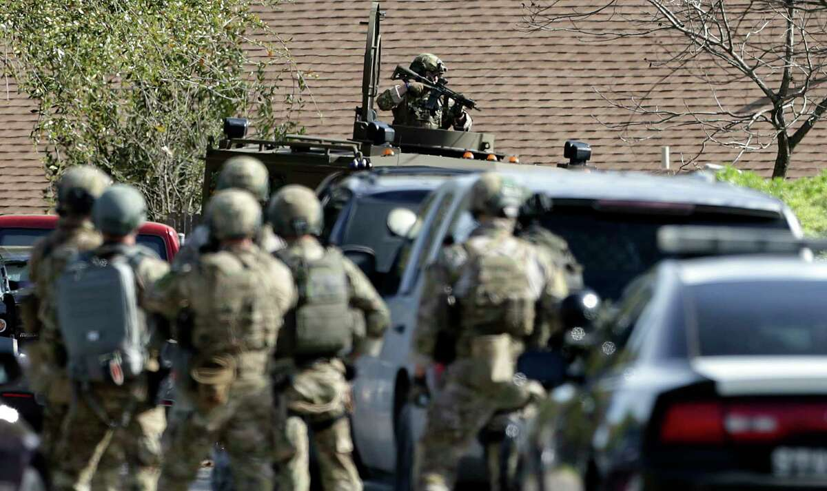 FBI SWAT members cover as the home is breached at the scene of Walnut and 2nd Street in Pflugerville where bombing suspect lived on March 21, 2018.