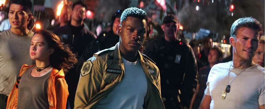 "This image released by Universal Pictures shows, foreground from left, Cailee Spaeny, John Boyega and Scott Eastwood in a scene from ""Pacific Rim Uprising."" (Legendary Pictures/Universal Pictures via AP) Photo: Legendary Pictures / Copyright: © 2017 Universal Studios. ALL RIGHTS RESERVED."