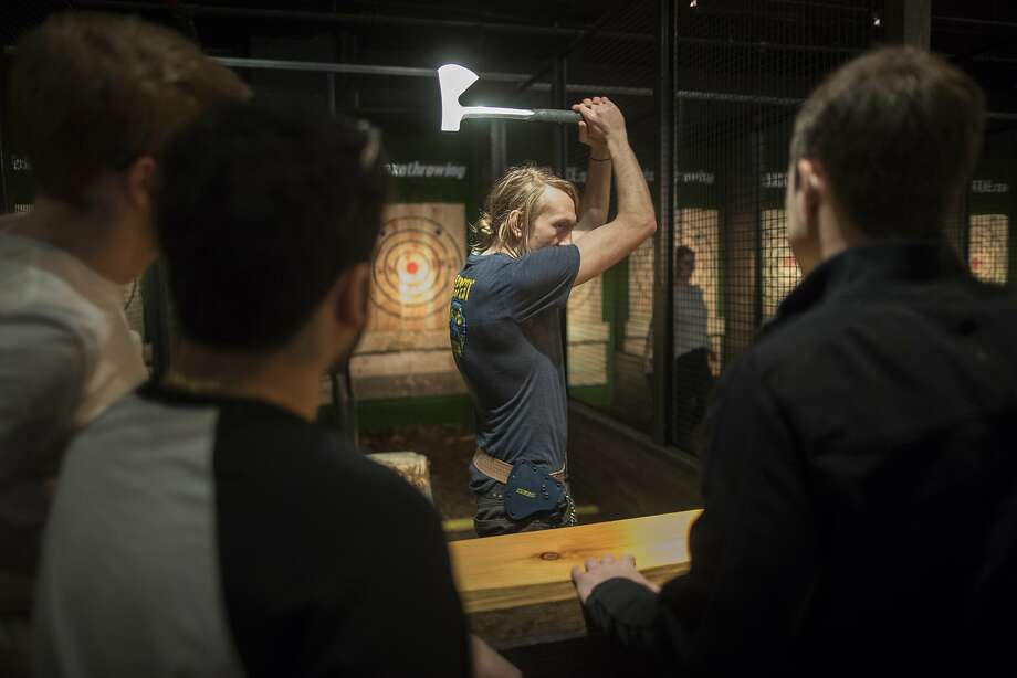 """In this March 3, 2018, photo, an """"axepert,"""" center, gives contestants instruction on hatchet throwing techniques and the rules of the game at the Kick Axe Throwing venue in the Brooklyn borough of New York. Kick Axe Throwing is the first bar in New York City to pick up on a nationwide trend of ax throwing. (AP Photo/Mary Altaffer) Photo: Mary Altaffer, Associated Press"""