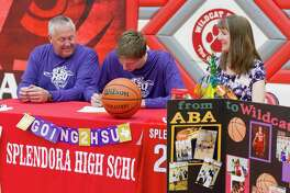 Splendora senior center Trey Wooldridge signs to play basketball for Hardin-Simmons beside his parents David and Karen during a signing ceremony at Splendora High School, Wednesday, March 21, 2018, in Splendora.