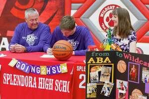 Splendora senior center Trey Wooldridge signs to play basketball for Hardin-Simmons beside his parents David and Karen during a signing ceremony at Splendora High School, Wednesday, March 21, 2018, in Splendora.