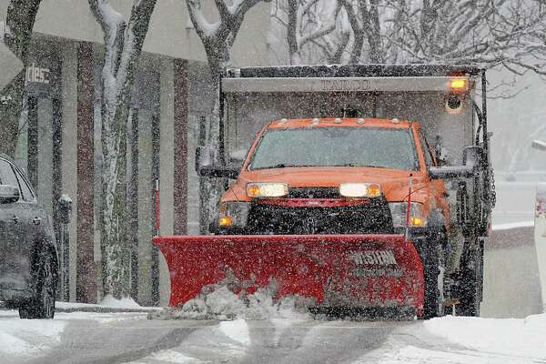 A plow truck clears snow on Railroad Avenue during the snowstorm that hit Greenwich, Conn., Wednesday, March 21, 2018.