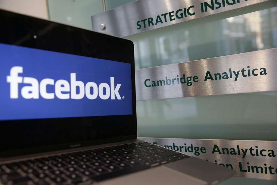 A laptop showing the Facebook logo is held alongside a Cambridge Analytica sign at the entrance to the building housing the offices of Cambridge Analytica, in central London on March 21, 2018.  Facebook expressed outrage over the misuse of its data as Cambridge Analytica, the British firm at the centre of a major scandal rocking the social media giant, suspended its chief executive.  / AFP PHOTO / Daniel LEAL-OLIVASDANIEL LEAL-OLIVAS/AFP/Getty Images Photo: DANIEL LEAL-OLIVAS, AFP/Getty Images