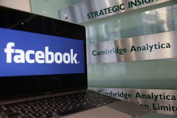 A laptop showing the Facebook logo is held alongside a Cambridge Analytica sign at the entrance to the building housing the offices of Cambridge Analytica, in central London on March 21, 2018.  Facebook expressed outrage over the misuse of its data as Cambridge Analytica, the British firm at the centre of a major scandal rocking the social media giant, suspended its chief executive.  / AFP PHOTO / Daniel LEAL-OLIVASDANIEL LEAL-OLIVAS/AFP/Getty Images