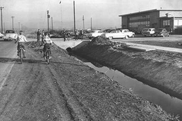 """From the Jan. 16, 1951, Chronicle: The road is the sidewalk on Weslayan, looking toward Westheimer, in front of Will Rogers Elementary School, because there are no sidewalks and the shoulder is muddy in rainy weather, but city officials hold out scant hope of improvement. So the school children, like those shown in this picture, have to go to school along the pavement that is loaded with auto traffic.   The city's public works department noted at the time that Weslayan was a former county road that was now inside city limits. As such, county construction methods did not provide a sidewalk right-of-way.    """"Unless property owners along the street are willing to move garages back five feet to provide sidewalk right of way, there is nothing we can do,"""" Public Works Director J.M. Nagle told the Chronicle.    Will Rogers Elementary, opened in 1950, was located at 3101 Weslayan, between Richmond and West Alabama. The site, along with HISD's headquarters and other related properties, was sold off in 2005."""