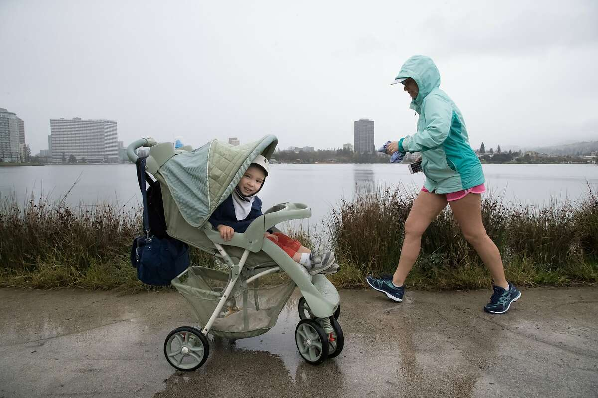 Roman Palomares, 2, peers from his stroller as Amelia Stoick runs by at Lake Merritt on Wednesday, March 21, 2018 in Oakland, CA. Mother Nailya was just off frame at left.
