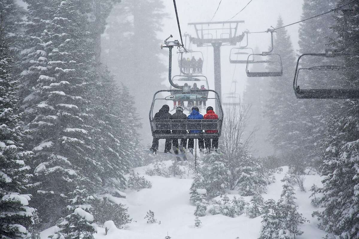 In this photo provided by Northstar California, skiers ride a chair lift as snow falls Thursday, March 1, 2018, at the Northstar California resort in Truckee, Calif.