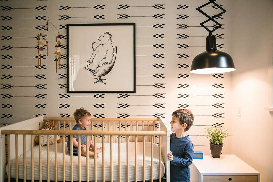 The Steins' nursery takes a simple yet sophisticated approach: Nate, 3, and baby sister Maya commune at the crib placed against a wall papered with a Zuni arrow design. Photo: Mason Trinca, Special To The Chronicle