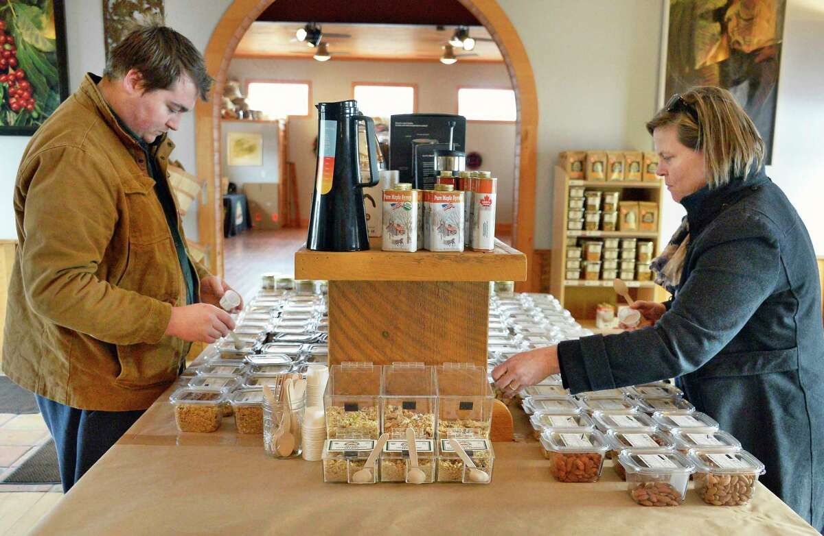 Samuel Moore, left, and his mother Diane Moore of Copake at the samples aisle in Tierra Farm's retail store Friday March 9, 2018 in Valatie, NY. (John Carl D'Annibale/Times Union)