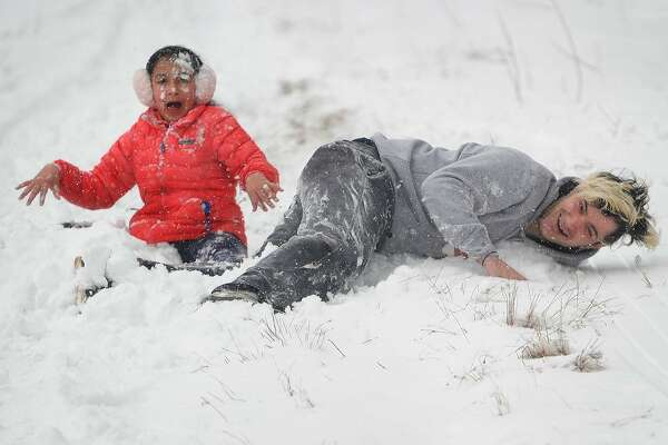 Jon Annuzzi and his neice, Sophia Fernandez, both of Fairfield, take a tumble during an afternoon of sledding on the Sturges Park sled hill in Fairfield, Conn. on Wednesday, March 21, 2018.