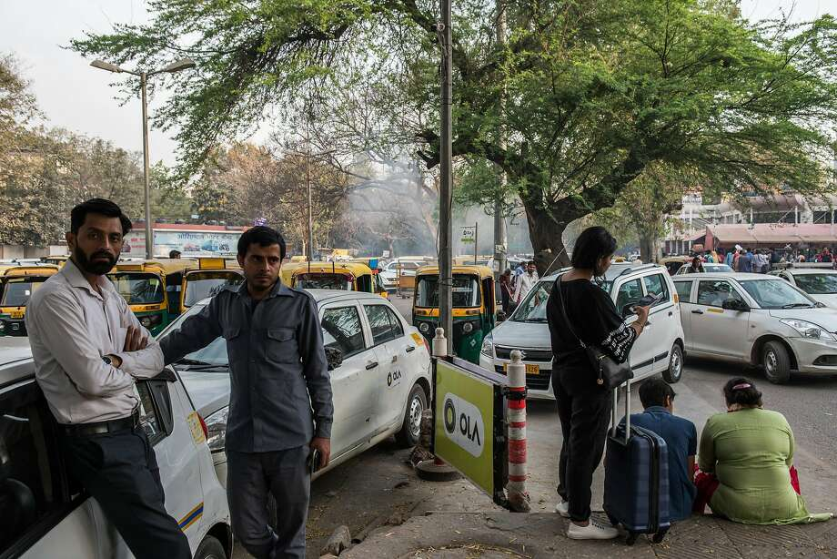 Drivers for Ola stand at a pickup point in New Delhi. Now the company is challenging Uber in Australia. Photo: REBECCA CONWAY, NYT