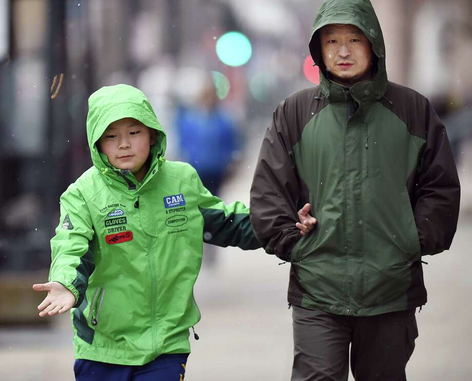 Michael Sun, 11, catches a snowflake walking down Church Street in New Haven with his father, Sam Sun, during the light snow of Wednesday's noreaster. The Suns are living in New Haven from northeast China while Sun's wife is a visiting scholar in forest economy at Yale University. Sun says it is much colder in northeast China than it is in New Haven. The National Weather Service has a winter storm warning to 6 a.m. Thursday. Photo: Catherine Avalone, Hearst Connecticut Media / New Haven Register