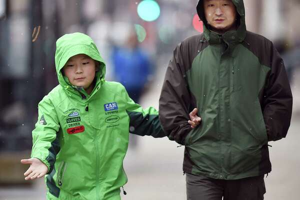 Michael Sun, 11, catches a snowflake walking down Church Street in New Haven with his father, Sam Sun, during the light snow of Wednesday's noreaster. The Suns are living in New Haven from northeast China while Sun's wife is a visiting scholar in forest economy at Yale University. Sun says it is much colder in northeast China than it is in New Haven. The National Weather Service has a winter storm warning to 6 a.m. Thursday.
