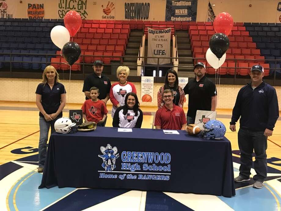 Greenwood softball player Payslee Sims (seated middle left) and football player Cade Bracey (seated middle right) sign their letters of intent to play at Sul Ross State University, Wednesday morning at the Greenwood High School gym. Courtesy photo.