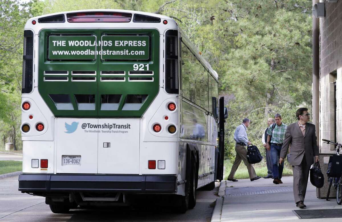 Commuters exit one of the buses of The Woodlands Express, a bus service to Houston, at the Research Forest park and ride location in The Woodlands on March 19.