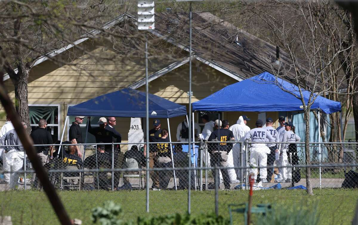 Federal officials work Wednesday, March 21, 2018 in front of Austin serial bombing suspect Mark Anthony Conditt's home in Pflugerville, Texas after bomb squads cleared bomb making equipment from the home.