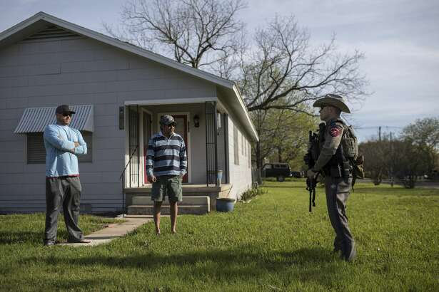 A Texas State Trooper speaks with men near the home of the parents of Austin bombing suspect Mark Anthony Conditt in Pflugerville, Texas, March 21, 2018. Authorities had identified Conditt, who blew himself up, via surveillance footage and other clues, the authorities said. (Tamir Kalifa/The New York Times)