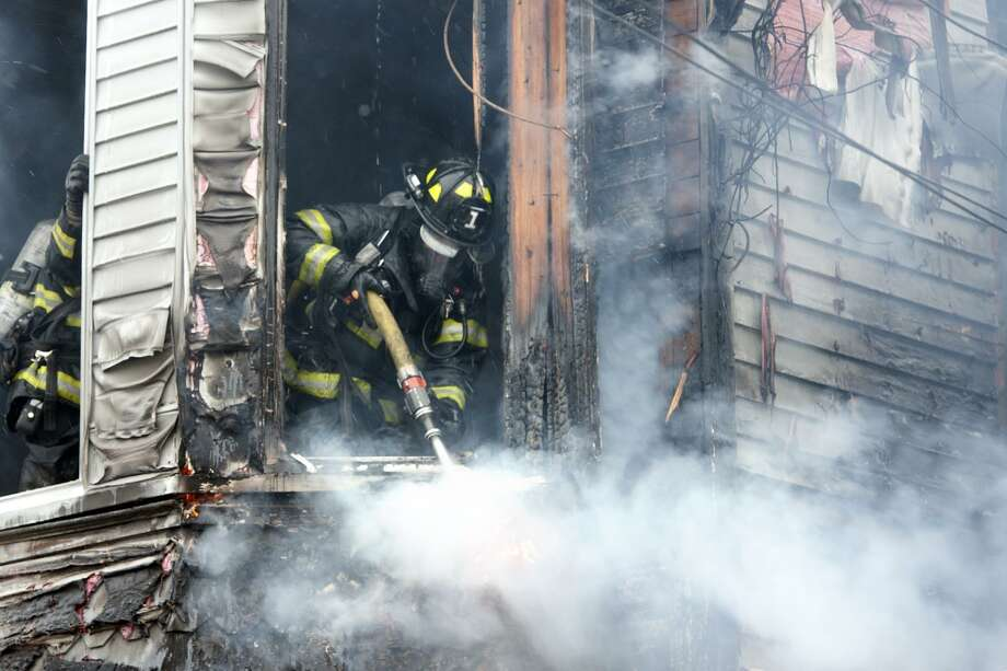 A Bridgeport firefighter works to extinguish a fire in an unoccupied home on Hanover St. in Bridgeport, Conn. March 21, 2018. The fire was brought under control in about a half an hour, and there were no reported injuries. Photo: Ned Gerard / Hearst Connecticut Media / Connecticut Post