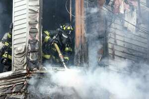 A Bridgeport firefighter works to extinguish a fire in an unoccupied home on Hanover St. in Bridgeport, Conn. March 21, 2018. The fire was brought under control in about a half an hour, and there were no reported injuries.