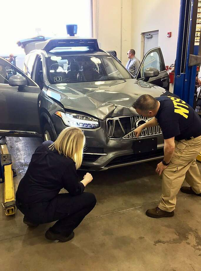 In this March 20, 2018, photo provided by the National Transportation Safety Board, investigators examine a driverless Uber SUV that fatally struck a woman in Tempe, Ariz. The fatality prompted Uber to suspend all road-testing of such autos in the Phoenix area, Pittsburgh, San Francisco and Toronto. (National Transportation Safety Board via AP) Photo: Associated Press