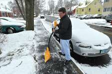Brian Sanders looks over his work after clearing his and his neighbors sidewalks of snow on Stuart Ave. in Norwalk Conn. on Wednesday March 21, 2018