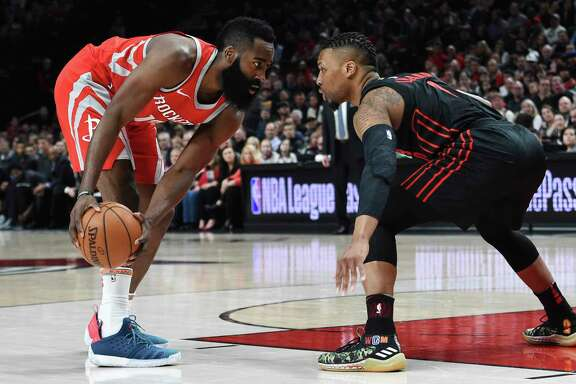 James Harden, left, lulls the Blazers' Damian Lillard into his trap Tuesday before launching his step-back 3.