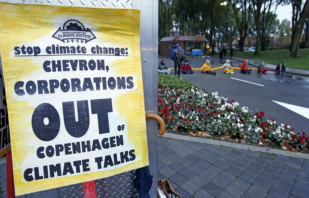 In this Dec. 7, 2009, file photo, demonstrators block the main entrance of Chevron Corp. in San Ramon. A federal judge presiding over lawsuits accusing big oil companies of lying about global warming is turning his courtroom into a classroom.