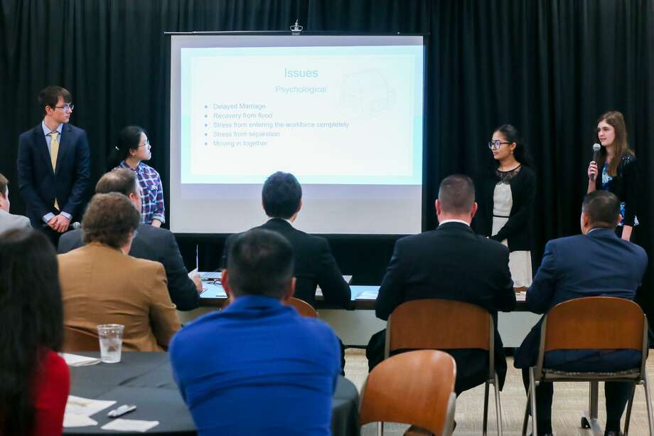 "Clark High School's Tony Holmes (standing, from left), 16, Chau Tran, 14, Melanie Quintero, 14, and Rachael Barner, 14, present their financial plan to a panel of judges (left) and the audience during the San Antonio CPA Society's 10th annual ""Jr. Duel in Ol' San Antonio,"" where six area high school teams competed in the finals at the Federal Reserve Bank of Dallas San Antonio Branch, 402, Dwyer Ave., on Saturday, March 3, 2018.  Teams were asked to write a financial plan to help a young couple get out of debt and plan for the future. MARVIN PFEIFFER/mpfeiffer@express-news.net Photo: Marvin Pfeiffer, Staff / San Antonio Express-News / Express-News 2018"