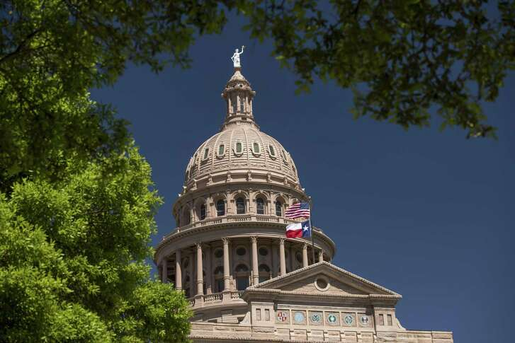 An American flag flies with the Texas state flag outside the Texas State Capitol building in Austin, Texas.