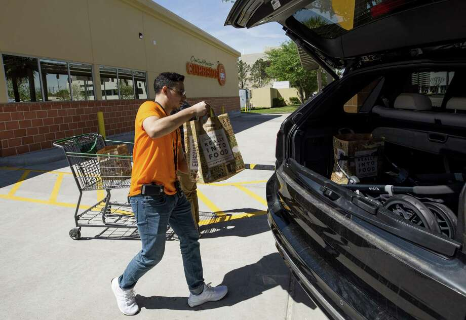 Central Market Curbside shopper Erik Martinez loads a costumer's order into the vehicle at one of the pick-up parking spots of the 3815 Westheimer Road location Wednesday, March 21, 2018, in Houston. This is the second Central Market location to offer Curbside pick-up service in Texas. ( Godofredo A. Vasquez / Houston Chronicle ) Photo: Godofredo A. Vasquez, Houston Chronicle / Houston Chronicle / Godofredo A. Vasquez