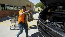 Central Market Curbside shopper Erik Martinez loads a costumer's order into the vehicle at one of the pick-up parking spots of the 3815 Westheimer Road location Wednesday, March 21, 2018, in Houston. This is the second Central Market location to offer Curbside pick-up service in Texas. ( Godofredo A. Vasquez / Houston Chronicle )