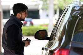 Central Market Curbside manager Rafael Moran talks to a costumer after loading up the vehicle with groceries at one of the pick-up parking spots of the 3815 Westheimer Road location Wednesday, March 21, 2018, in Houston. This is the second Central Market location to offer Curbside pick-up service in Texas. ( Godofredo A. Vasquez / Houston Chronicle )