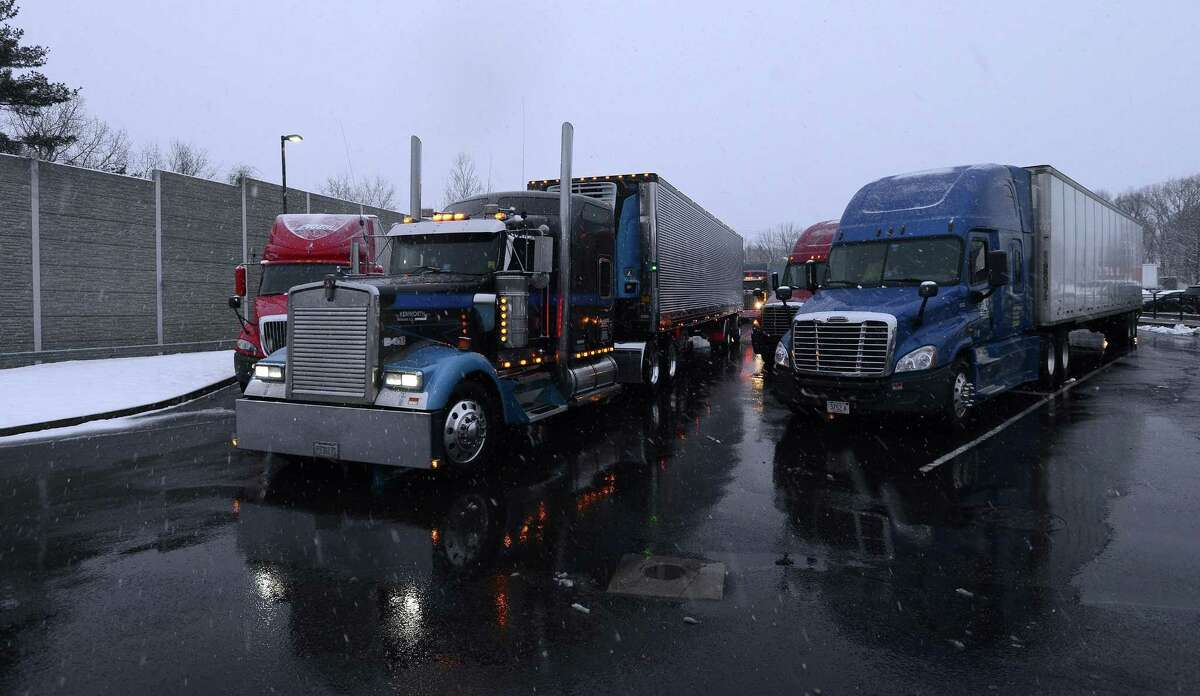 A driver pulls his rig thru the Darien Travel Plaza on I-95 South during a Spring Nor'easter on Tuesday, March 21, 2018 near Stamford. Connecticut. A Truck Travel Ban issued for the State of New York have long haul drivers pulling off the road to spend the night at the travel plaza, til the ban is lifted. An estimated 250 trucks are parked for the night.