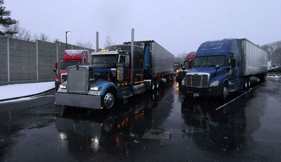 A driver pulls his rig thru the Darien Travel Plaza on I-95 South during a Spring Nor'easter on Tuesday, March 21, 2018 near Stamford. Connecticut. A Truck Travel Ban issued for the State of New York have long haul drivers pulling off the road to spend the night at the travel plaza, til the ban is lifted. An estimated 250 trucks are parked for the night. Photo: Matthew Brown / Hearst Connecticut Media / Stamford Advocate