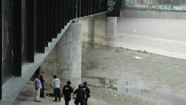 In this June 7, 2010 file photo, Mexican federal police and forensic experts stand next to the body of 14 year-old Sergio Adrian Hernandez Guereca, under the Paso Del Norte border bridge, as US officials watch from the US side at right, in Ciudad Juarez, northern Mexico. The Supreme Court appears to be evenly divided about the right of Mexican parents to use American courts to sue a U.S. Border Patrol agent who fired across the U.S.-Mexican border and killed their teenage son.