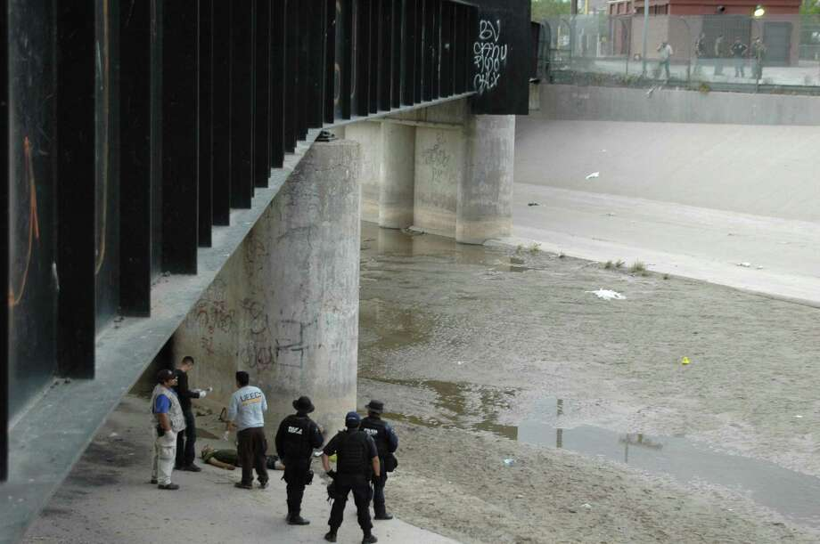 In this June 7, 2010 file photo, Mexican federal police and forensic experts stand next to the body of 14 year-old Sergio Adrian Hernandez Guereca, under the Paso Del Norte border bridge, as US officials watch from the US side at right, in Ciudad Juarez, northern Mexico. The Supreme Court appears to be evenly divided about the right of Mexican parents to use American courts to sue a U.S. Border Patrol agent who fired across the U.S.-Mexican border and killed their teenage son. Photo: /AP / AP2010