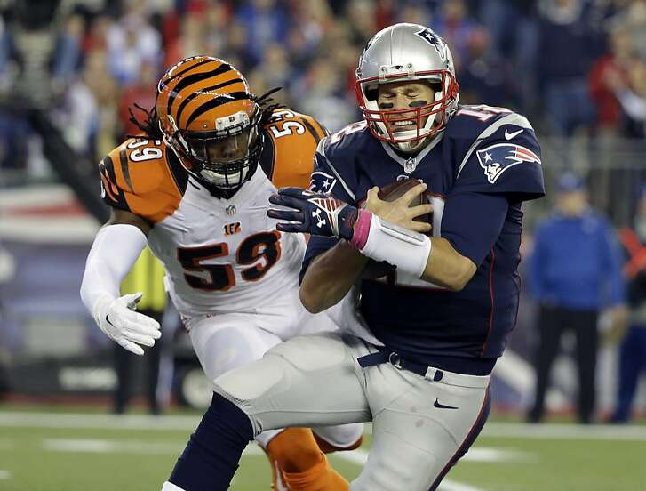 New England Patriots quarterback Tom Brady goes down in front of Cincinnati Bengals outside linebacker Emmanuel Lamur (59) in the first half of an NFL football game Sunday, Oct. 5, 2014, in Foxborough, Mass. (AP Photo/Steven Senne)