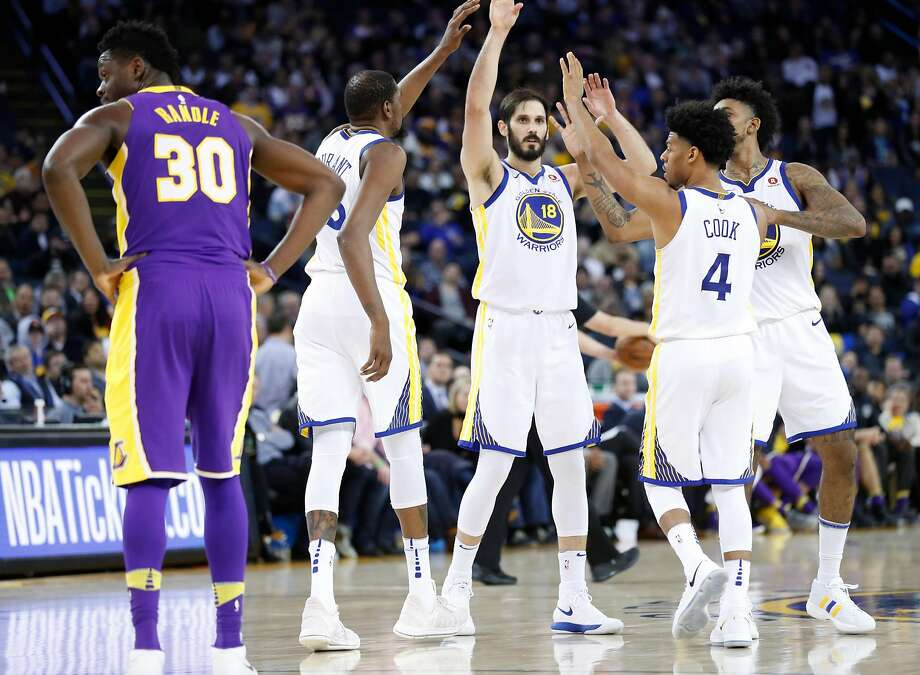 Golden State Warriors' Kevin Durant, Omri Casspi, Quinn Cook and Nick Young high five after Los Angeles Lakers' Julius Randle fouled in 4th quarter during Warriors' 117-106 win in NBA game at Oracle Arena in Oakland, Calif., on Wednesday, March 14, 2018. Photo: Scott Strazzante, The Chronicle