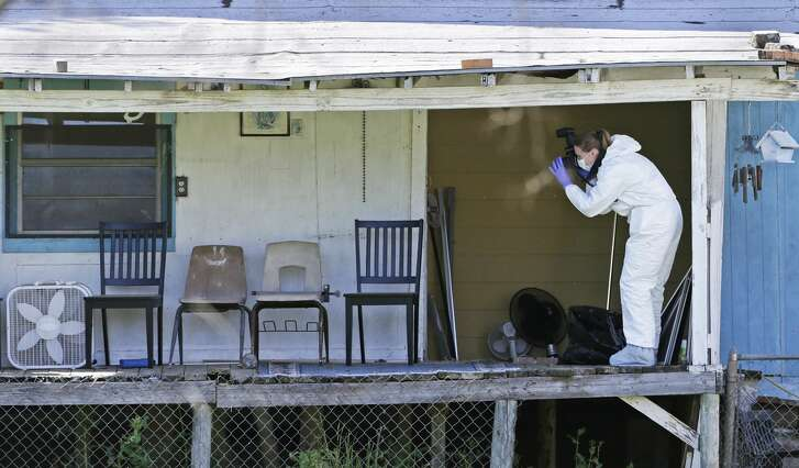 Crime scene photographers work through the backyard at the scene of Walnut and 2nd Street in Pflugerville where bombing suspect lived  on March 21, 2018.